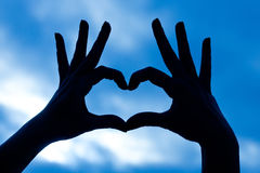 Love shape hand silhouette in sky Royalty Free Stock Photos