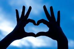 Love shape hand silhouette in sky. Love shape hand silhouette in blue sky Royalty Free Stock Photos