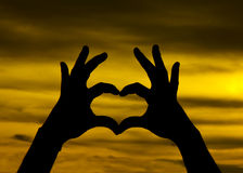 Love shape hand silhouette in sky Royalty Free Stock Photo