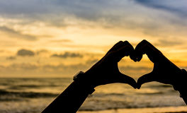 Love shape hand silhouette in sky Royalty Free Stock Image