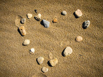 Love Shape on Sand. Love Shape made with little rocks on the wet sand Stock Photography
