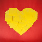 Love shape by yellow notes on red paper background Stock Photos