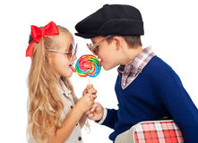 Love is sharing. Childhood sweethearts with a lollipop and vintage clothes Stock Photography