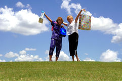 We love shopping. Two happy senior women holding up shopping bags outdoors stock photo