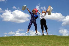 We love shopping. Two happy senior women holding up shopping bags jumping outdoors stock photography