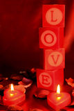 Love shrine. The word LOVE spelt out on candles, with two heart-shaped candes in the foreground and a red backdrop royalty free stock image