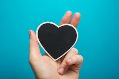 Love sign. Black board heart in woman hands on blue background. Copy space for text Stock Image