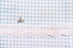 Love sign on blue dogtooth  fabric with lace. Valentine's Day Stock Image