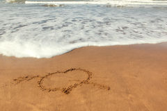 Love sign (heart) written on sand. Love sign (heart with an arrow) written on sand with ocean waves flowing Royalty Free Stock Images