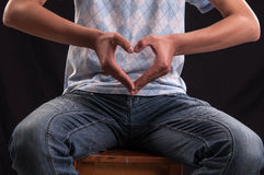 Love sign made with the hands by a young man Royalty Free Stock Photo