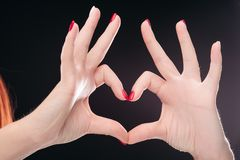 Love sign making by hands with red manicured nails on black studio background. Crop of two hadns together showing heart by fingers and gesturing symbol of amour royalty free stock photos