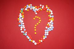 Love sign with question mark inside made with medicin. medicin cost and efficiency concept.  Royalty Free Stock Photos