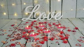 Love sign with red hearts around and candles lighted up. Lights on backround. Valentines day. Love sign with red hearts around and candles lighted up on the stock footage