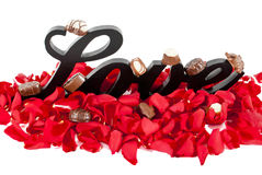 Love Sign with Rose Petals and Chocolates Stock Photos