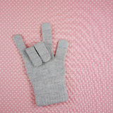 The love sign showing by knitted grey glove. On polka dots pink fabric background Royalty Free Stock Photography