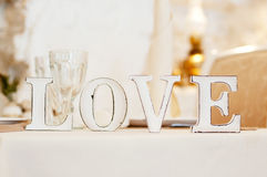 Love sign on table. Decor in restaurant. Light beige Royalty Free Stock Photography