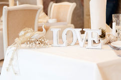 Love sign on table. Decor in restaurant. Peacock Royalty Free Stock Photography