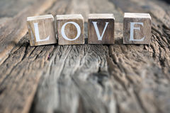 Love sign. On a wooden table made out of old barn wood Royalty Free Stock Photos