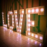 Love Sign Word Lighting Bulbs Against Barn Wall. Lighting Stock Photography