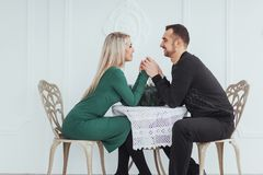 Love sitting at the table couple man and woman with wineglasses on white background in the restaurant. valentines dinner Royalty Free Stock Photo