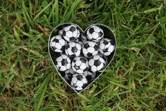 Love Soccer. Heartfull of chocolate footballs on a grass pitch royalty free stock photography