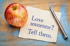 Love someone? Tell them. Handwriting on a napkin with a fresh apple Royalty Free Stock Photos