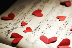 Love song. Closeup of red paper hearts on yellowed music book Royalty Free Stock Photos