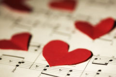 Love song. Closeup of red paper hearts on yellowed music book Royalty Free Stock Images