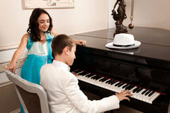 Love Song. Lovely young lady admiring his boy performing at a grand piano. Please see more images from the same shoot Stock Photography