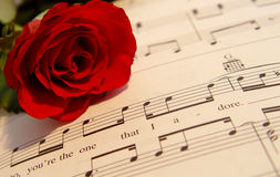 Love song. Red rose resting on a love song Royalty Free Stock Image