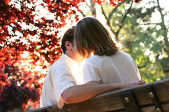 Love spark. Couple kissing on a park bench, light streaming in betwen them... How romantic Stock Photography