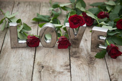 Love spelled out with roses. Metallic love word on wooden background Royalty Free Stock Photo