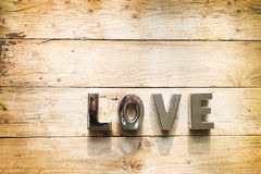 Love spelled out on wooden background Stock Photos