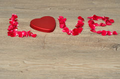 Love spelled with red rose petals and a heart shape tin Stock Images