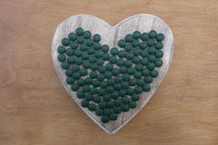 Love Spirulina, conceptual artistic composition with a wooden heart and many pills. Healthy Spirulina that we love with an artistic composition on a wooden board Royalty Free Stock Images
