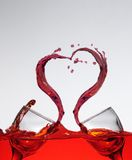 Love splash wine. Splash in love form created by wine from two glass of wine on wine tank with wave Royalty Free Stock Photos