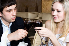 Love story... The man and the girl drink wine at restaurant Royalty Free Stock Image