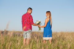 Love story. Beautiful young couple walking in meadow, outdoor Stock Photo