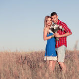 Love story. Beautiful young couple walking in meadow, outdoor Royalty Free Stock Image