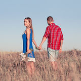 Love story. Beautiful young couple walking in meadow, outdoor Royalty Free Stock Photos
