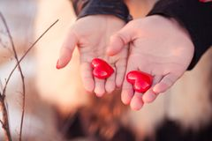 Love story concept. Woman's and men's hands holding pair of hearts as a symbol of love Stock Photo