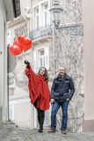 Love story. A young men and a young women with red accessories are walking in the city Stock Images
