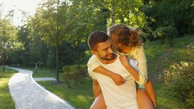 Love story in the park. Girl sitting on the back of her boyfriend. Love games. Happy man and woman stock footage
