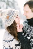 Love story in the winter forest. Young romantic couple outdoor. Young man touches the face of his pretty woman. Valentine`s Day c stock photo