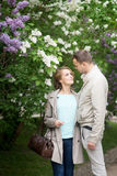 Love story, young couple in lilac garden. Romance relationship Stock Image