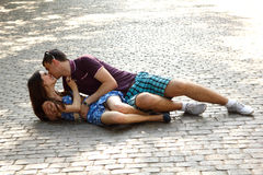 Love story of young couple lying on stone paving hug and kiss Royalty Free Stock Images