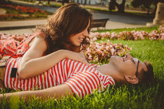 Love story, young guy and girl lying on green grass, embracing each other in park and spending time together Stock Image