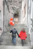 Love story. A young men and a young women with red accessories are walking in the city Royalty Free Stock Photo
