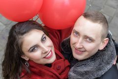 A young man and a young woman with red accessories a. Love story. A young men and a young women with red accessories are walking in the city Stock Images