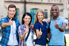 We love studying!. Four happy young people showing their thumbs up and smiling while standing close to each other outdoors Stock Images